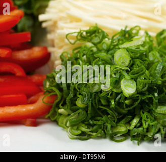 Closeup photo of fresh sliced green onions used as sushi ingredients placed in white plate along with mushrooms - Stock Photo