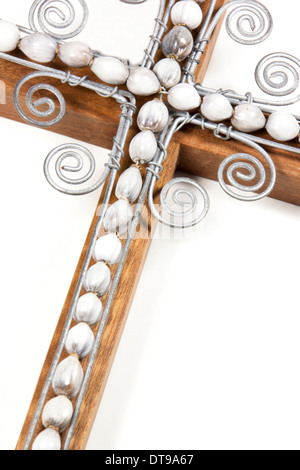 closeup of hand made wire cross decorated with beads attached to wooden cross on white - Stock Photo