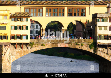 Ponte Vecchio with late afternoon sunlight and crowd of tourists, one rower under bridge - Stock Photo