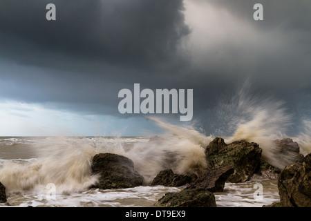 Waves crashing around rocks during a storm - Stock Photo