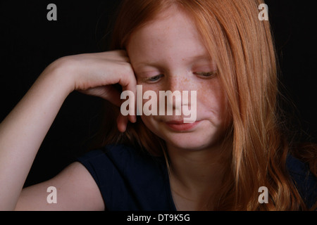 a freckled red haired little girl with her hand up to her face looks down to the ground. landscape isolated on black - Stock Photo