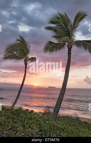 Makena Beach view of setting sun over the offshore islands of Kahoolawe and Molokini on Hawaii's island of Maui. - Stock Photo