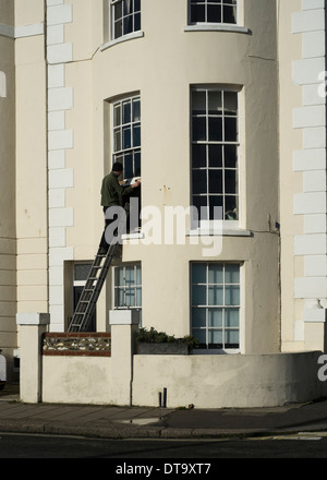 A man repairing sash windows on a period building on Worthing seafront. Picture by Julie Edwards - Stock Photo