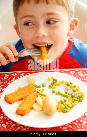 Young Boy Eating Fish fingers and Vegetables - Stock Photo