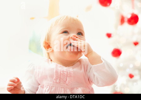 Portrait of Baby Girl with Finger in Mouth and Tongue Sticking Out - Stock Photo