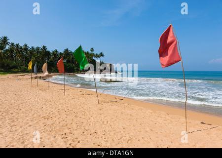 Colorful flags on the beach, near Duwemodara, Galle region, Southern Province, Sri Lanka - Stock Photo