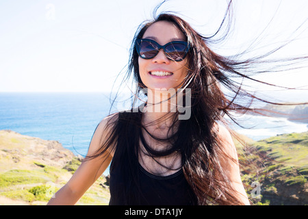 Smiling Woman on Hilltop with Windswept Hair - Stock Photo