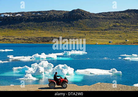 Man of the Inuit people riding a quad bike, ATM, parked on the shore of the Beaufort Sea, Arctic Ocean, Victoria - Stock Photo