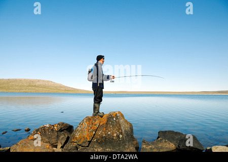 Men of the Inuit people fishing in a lake, Victoria Island, formerly Holman Island, village of Ulukhaktok, Northwest - Stock Photo