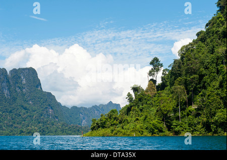 Forested karst limestone mountains with jungle vegetation rising from the water, Rachabrapha reservoir, Chiao Lan - Stock Photo