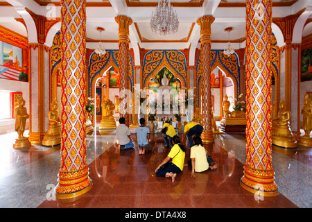 Visitors praying in front of the altar, columns, Wat Chalong temple, Phuket, Thailand - Stock Photo