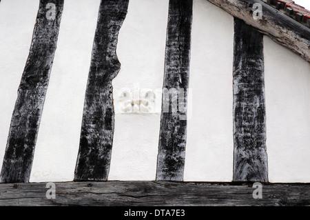 Fleur de lis, Wool merchant's mark, on the wall of a timber framed building in Lavenham, Suffolk. - Stock Photo