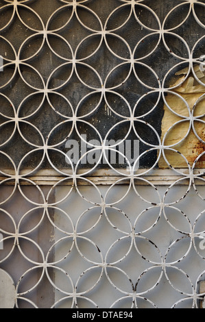 Rusty metal door with geometric circles motif and paint stained glass background. - Stock Photo