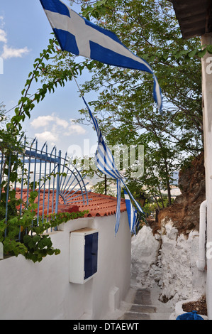 Narrow alleyway with greek flags and small house in the traditional Anafiotika neighborhood, Athens, Greece. - Stock Photo