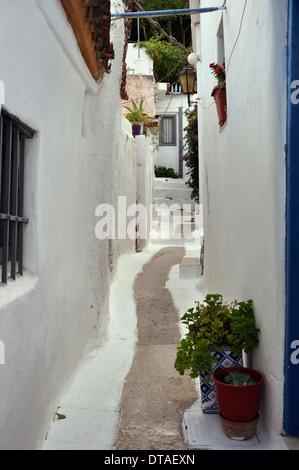 White painted narrow street and small houses in the traditional Anafiotika neighborhood of Plaka, Athens, Greece - Stock Photo