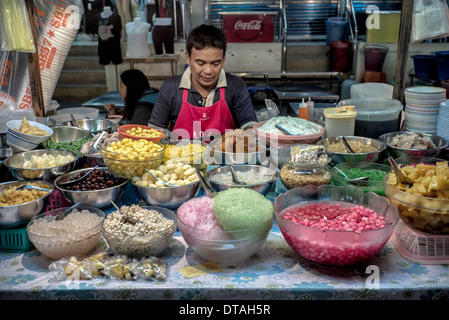 Thailand street market stall with vendor selling various fruit and sweet dishes traditional to the region. Thailand - Stock Photo