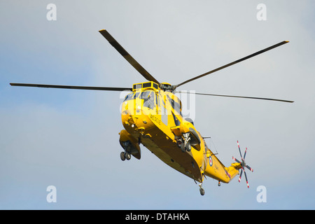 A yellow RAF Sea King rescue helicopter in the air. - Stock Photo