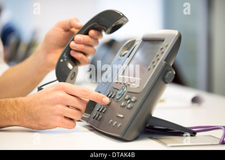 Close-up of hands businessman take the phone of the hook, in office - Stock Photo
