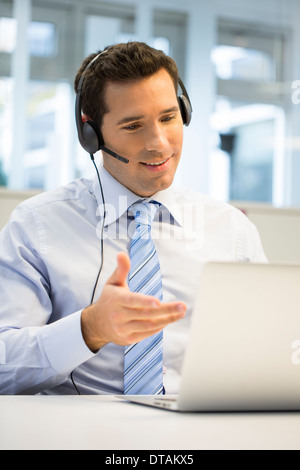 Businessman in office on phone with headset, hotline - Stock Photo