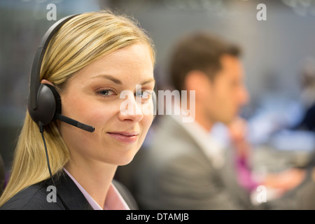 Portrait of Businesswoman in office on phone with headset, looking camera - Stock Photo