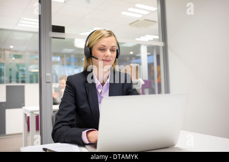 Businesswoman in office on phone with headset, video conference - Stock Photo