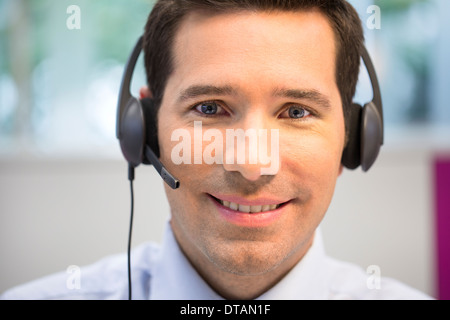 Portrait of businessman in office on phone with headset, looking camera - Stock Photo
