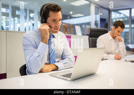 Businessman in office on phone with headset, call conference - Stock Photo