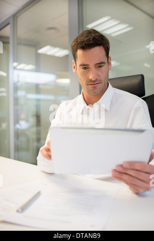Businessman in office working on computer tablet - Stock Photo