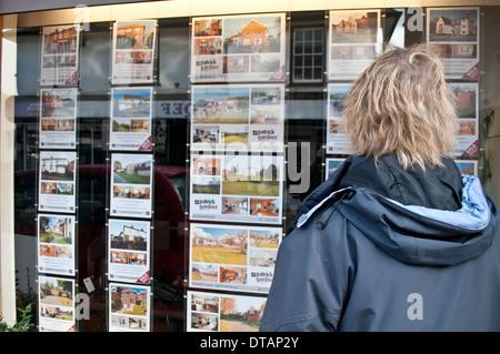 Woman looking at Estate Agent window, Leatherhead, Surrey, England, UK - Stock Photo