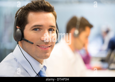 Portrait of operator in office on phone with headset, looking camera - Stock Photo