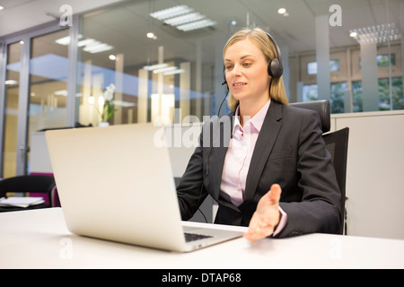 Pretty Businesswoman in office on phone with headset, video conference - Stock Photo