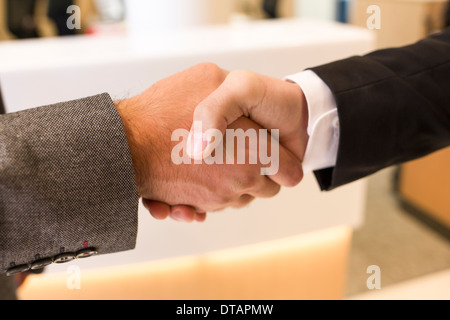 Two businessmen shaking Hands in office - Stock Photo