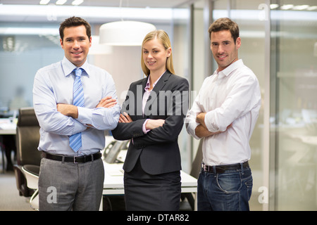 Portrait of smiling business team in office, looking camera - Stock Photo