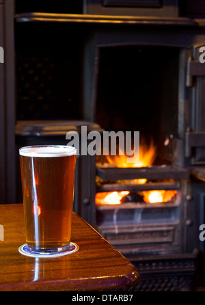 A pint of bitter on a pub table, with open fire in the background - Stock Photo