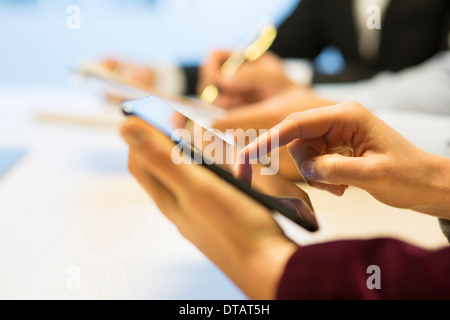 Close-up of Businesswoman hands writing on digital tablet during a meeting - Stock Photo