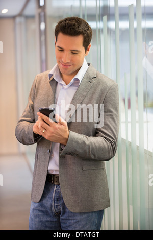 Handsome businessman sending a message on cell phone in office - Stock Photo
