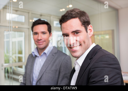 Portrait of Two smiling businessmen in office, looking camera - Stock Photo