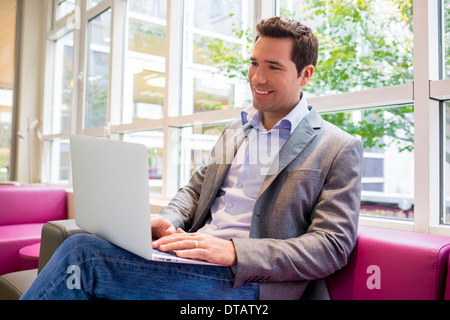 Happy smiling young Businessman working with Laptop on sofa - Stock Photo