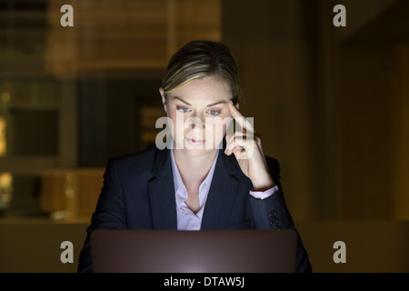 Portrait of businesswoman working late in his office on laptop - Stock Photo