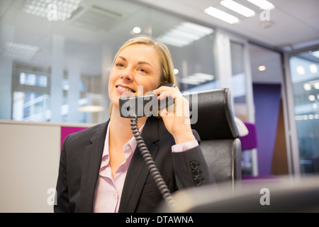 Blonde Businesswoman telephoning in her office - Stock Photo