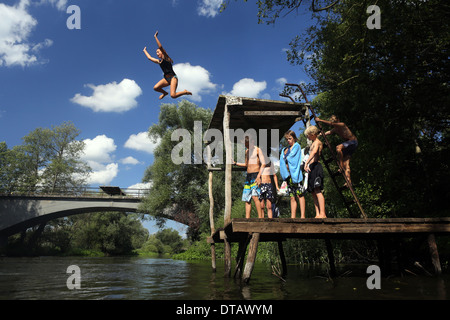 Briescht, Germany, girl jumps from a platform into the water - Stock Photo