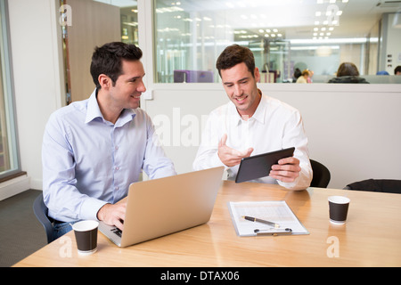 Two casual businessmen working together in office with laptop and tablet pc - Stock Photo