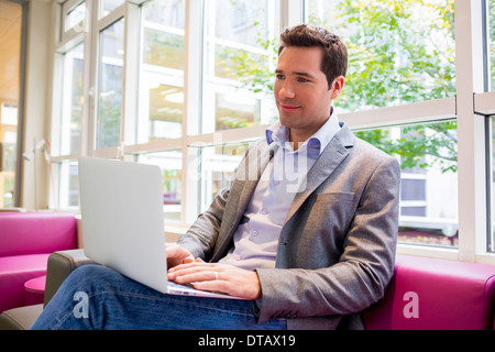 Handsome young Businessman working with Laptop on sofa in office - Stock Photo