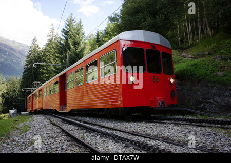 A red and white train of the Montenvers rack railway climbs through the trees above Chamonix in France. - Stock Photo