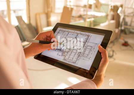 Architect woman drawing with stylus on electronic tablet in Construction site - Stock Photo