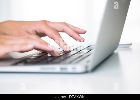 Close-up on woman hands typing on keyboard laptop computer, office, desk - Stock Photo