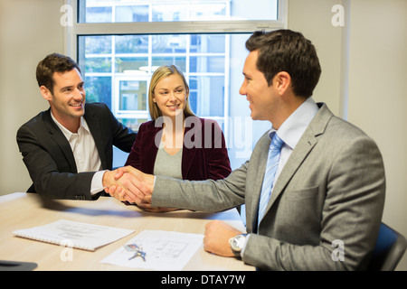 Couple in meeting room with financial adviser, contract, handshake, new property owners - Stock Photo