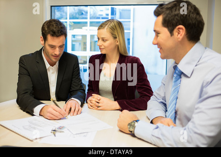 Young couple signing contract in office withe real-estate, new property owners - Stock Photo