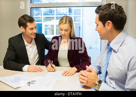 Young couple signing contract in office withe real-estate - Stock Photo