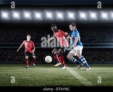 Soccer players with ball on field - Stock Photo